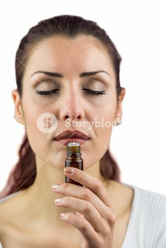 Close-up of woman smelling bottle of medicine