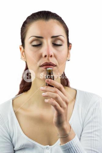 Woman with eyes closed and smelling bottle of medicine
