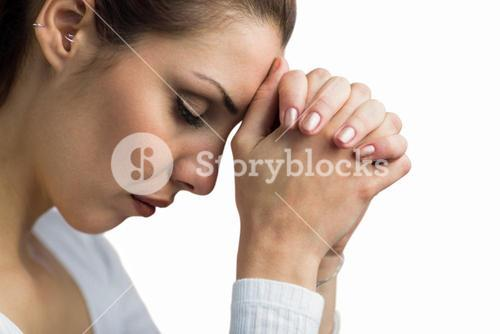 Peaceful woman praying with joining hands and eyes closed