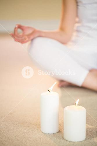 Low section of woman in yoga pose with illuminated candles