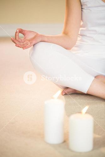 Low section of meditating woman with illuminated candles