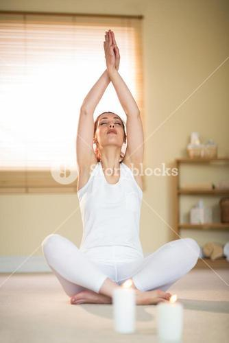 Woman in yoga pose with eyes closed and hands joined