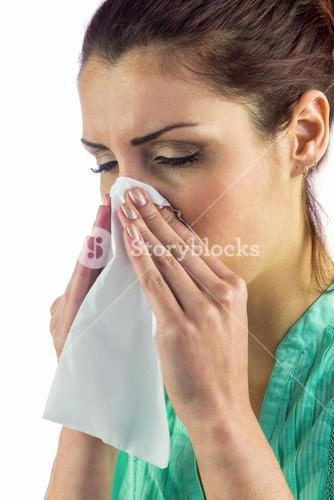 Close-up of sneezing woman with eyes closed and tissue on mouth