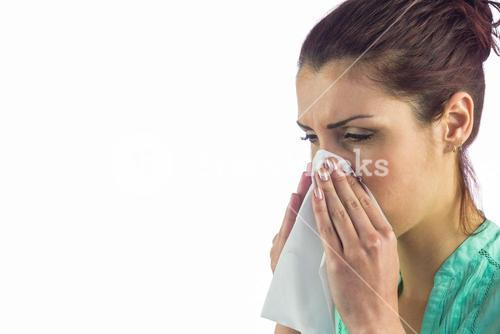 Close-up of sneezing woman with tissue on mouth