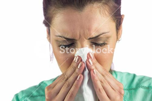 Close-up of woman suffering from cold with tissue on mouth