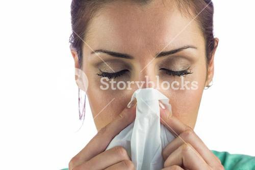 Close-up of woman suffering from blowing nose with tissue on mouth