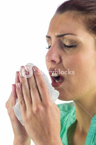 Sneezing woman holding tissue with mouth open