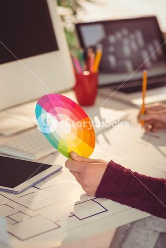Businesswoman drawing plans and hold a color watch