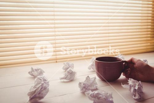 Hands holding coffee cup next to paper balls
