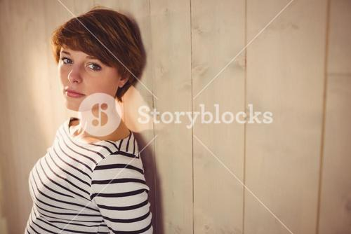 Pretty young woman backed on wall