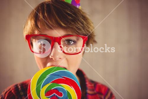 Pretty young woman eating lollipop