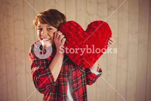 Pretty woman holding a heart pillow
