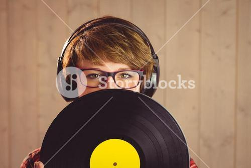 Young woman hiding herself behind vinyl