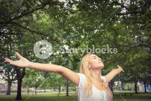 Woman with arms raised in park