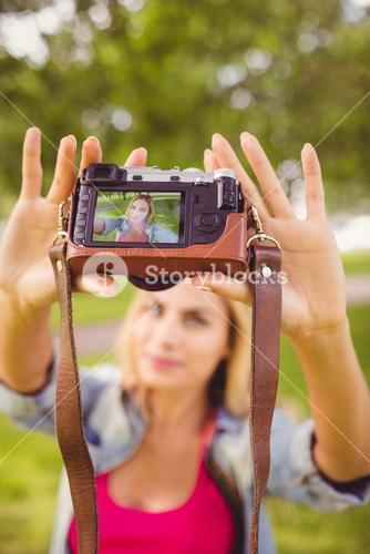 Woman taking self portrait with camera
