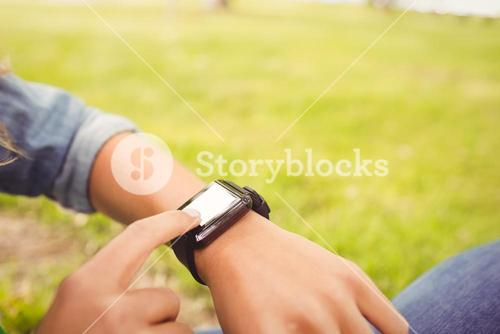Mid section of woman touching smart watch