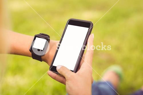 Cropped hands wearing smart watch and holding smartphone