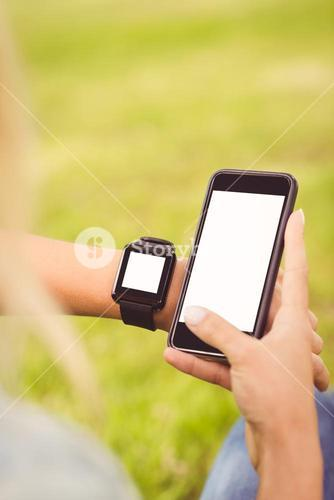 Cropped hands of person wearing smart watch and holding smartphone