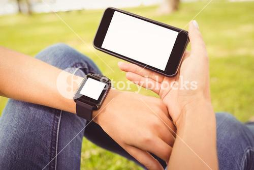 Low section of person wearing smart watch and holding smartphone