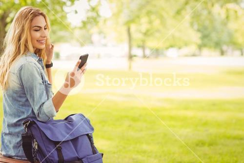 Smiling woman using smartphone at park