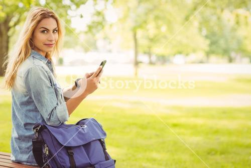 Portrait of woman holding smartphone at park