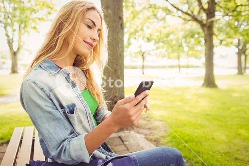 Beautiful woman using smartphone at park