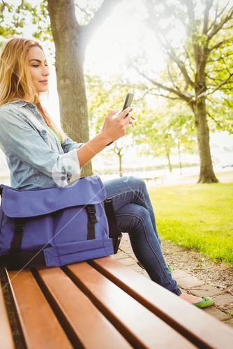 Happy woman using smartphone at park