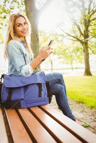 Portrait of smiling woman holding smartphone at park