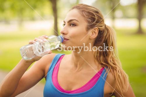 Woman drinking water in park