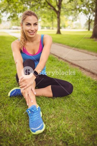 Smiling woman with legs crossed in park
