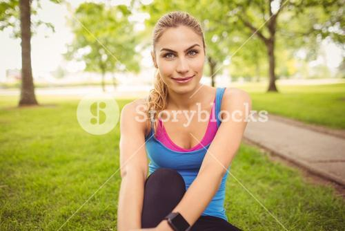 Portrait of smiling woman with legs crossed in park
