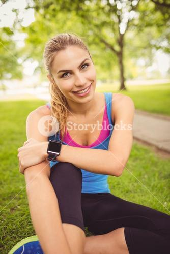 Portrait of happy woman with legs crossed in park