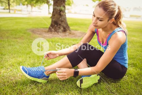 Woman tying shoelace at park