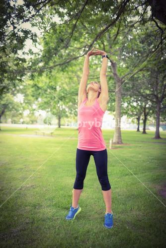Full length of woman exercising with arms raised