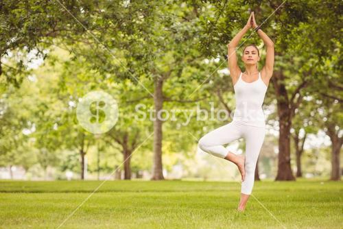 Woman standing in tree pose at park
