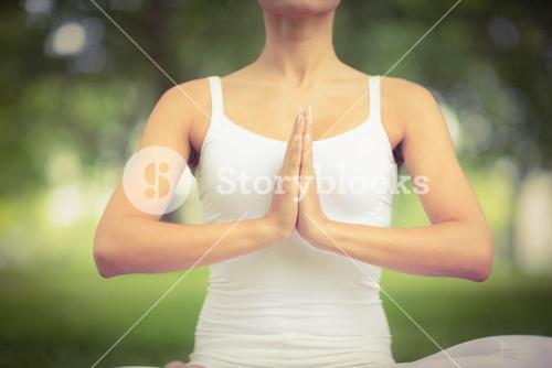 Mid section of woman with hands clasped