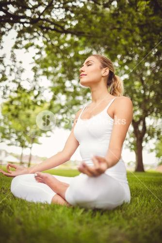 Woman meditating with eyes closed while sitting in lotus pose