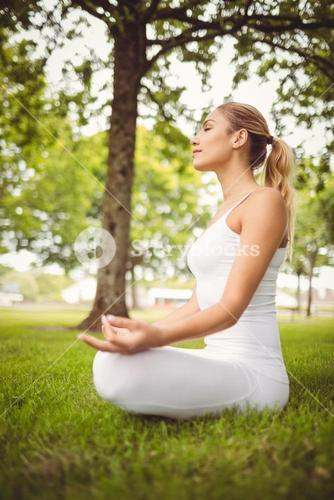 Side view of woman meditating while sitting in lotus pose