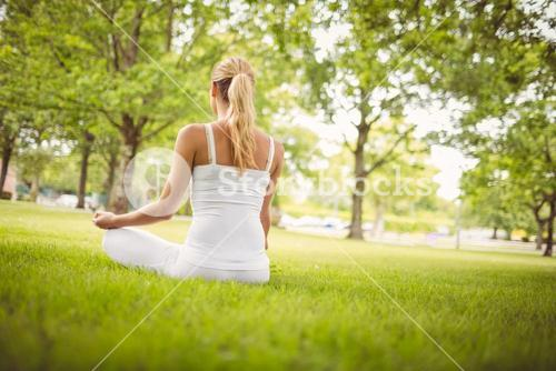 Rear view of woman meditating while sitting in lotus pose