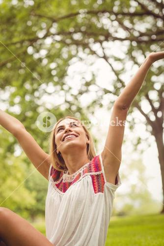 Smiling woman with hands raised