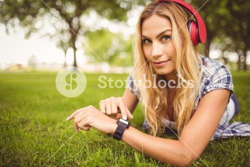 Portrait of smiling woman listening to music and touching wristwatch