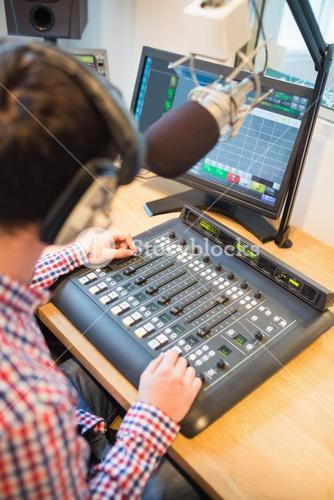 Radio host using sound mixer on table