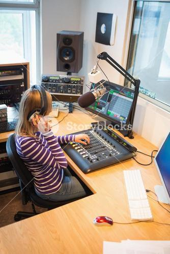 High angle view of female radio host operating sound mixer
