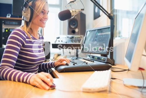 Female radio host using computer while broadcasting