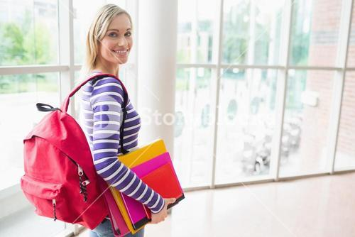 Confident female student with backpack and books