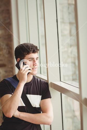 Male student talking on mobile phone in college