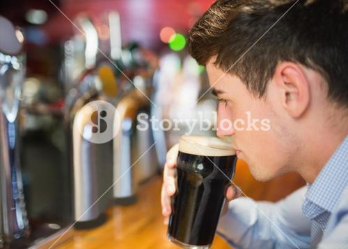 Man with drink at bar counter