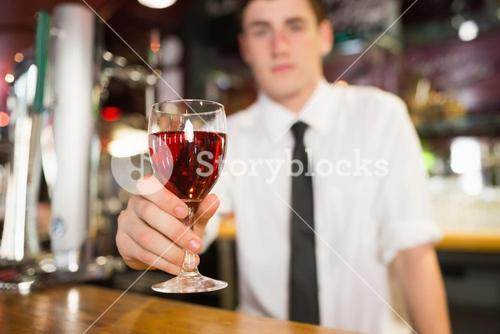 Male bartender serving alcohol