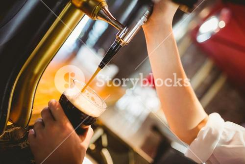 Cropped hand of barkeeper dispensing beer