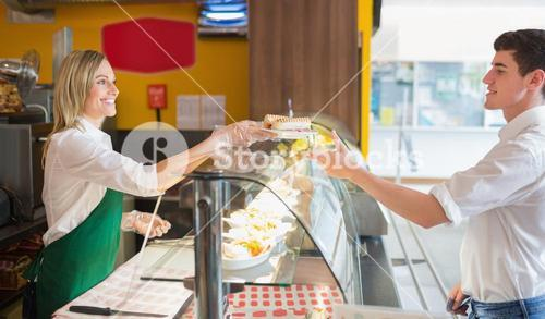 Female shop owner serving sandwich to male customer